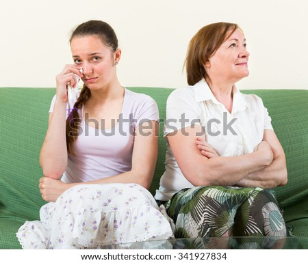 Sad adult daughter against mature woman  after conflict - stock photo