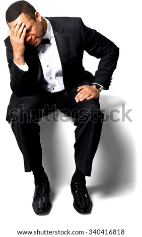 Sad African man with short black hair in evening outfit with hands on thighs - Isolated - stock photo