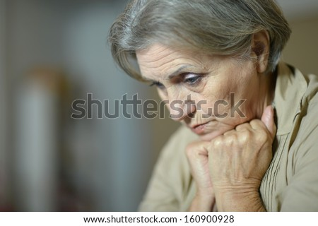 sad aged woman at home - stock photo