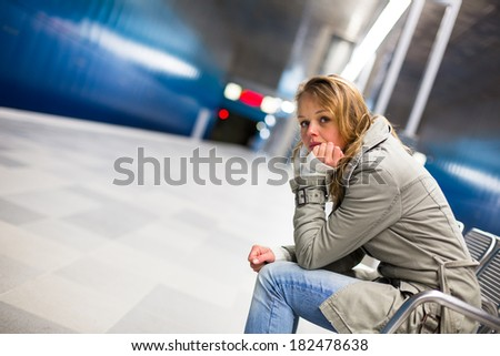 Sad and alone in a big city - Depressed young woman sitting in a metro station, feeling sorrow, regret - stock photo