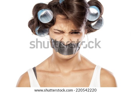 sad and angry woman with curlers and adhesive tape over her mouth - stock photo