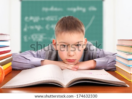 Sad and Bored Schoolboy in the Classroom - stock photo