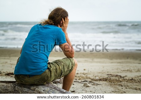 Sad and depressed man alone at the beach - stock photo