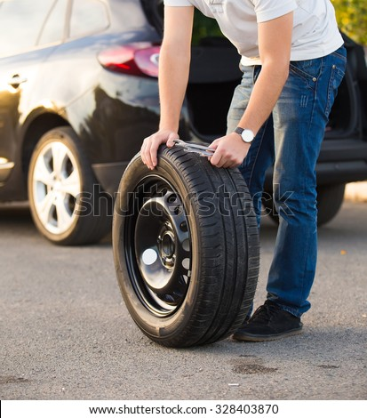 Sad and depressed man  near car with punctured tire - stock photo