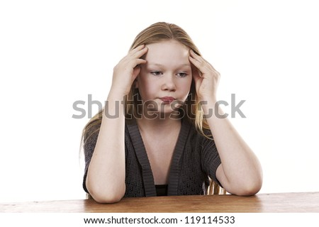 Sad and frustrated young girl sitting by table on white background