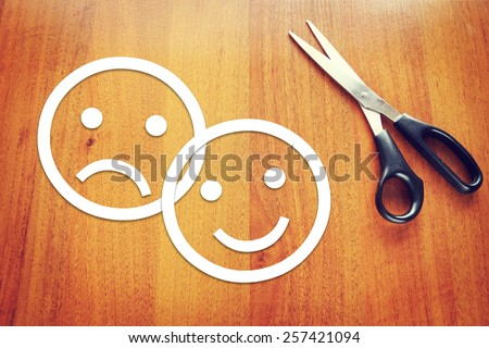 Sad and happy emoticons made of paper on the desk. Concept of various emotions - stock photo