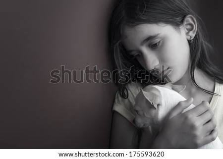 Sad and lonely girl and her small dog leaning against a wall - stock photo