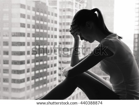 Sad and lonely woman in the city sitting next to a window.  - stock photo