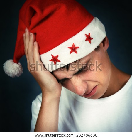 Sad and Painful Teenager in Santa's Hat On the Dark Background - stock photo