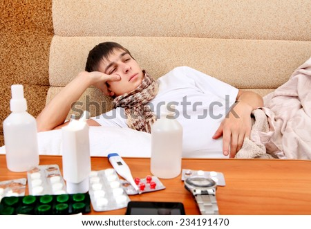 Sad and Sick Teenager on the Sofa at the Home with Pills on foreground - stock photo