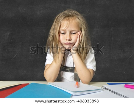 sad and tired cute junior schoolgirl with blond hair sitting in stress working doing homework looking bored and overwhelmed in children education at school and academic performance - stock photo
