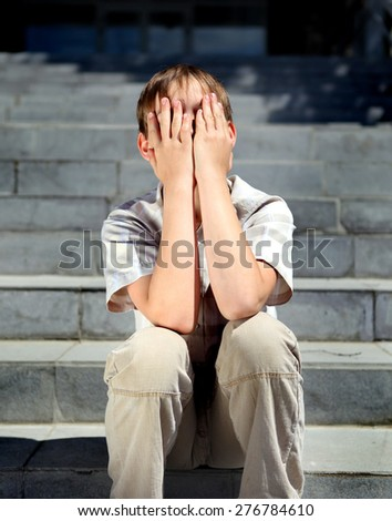 Sad and Troubled Kid sit on the Landing Steps outdoor