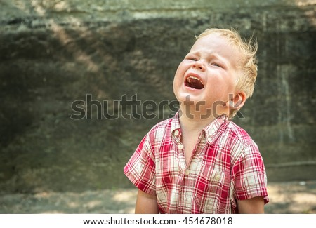 sad and unhappy child boy in the street is crying. Upset problem child with head in hands. concept for bullying, depression stress or frustration. concrete wall as  background - stock photo