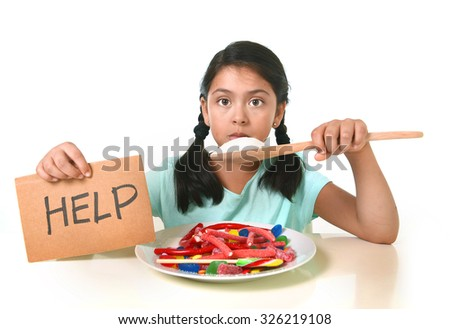 sad and vulnerable hispanic female child asking for help  eating dish full of candy and gummies holding sugar spoon in sweet abuse dangerous diet and unhealthy nutrition concept isolated on white - stock photo