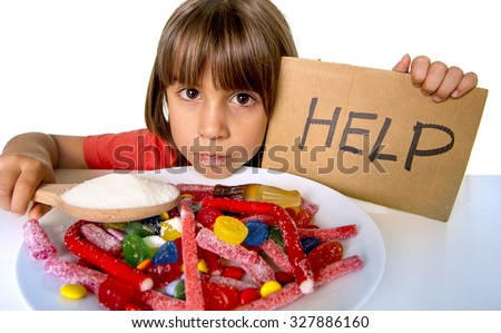 sad and vulnerable 4 or 5 years old female child asking for help  eating dish full of candy holding sugar spoon in sweet abuse dangerous diet and unhealthy nutrition concept isolated on white - stock photo
