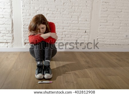 sad and worried pregnant teenager girl or young desperate woman looking to positive pink pregnancy test scared and devastated on floor in unwanted baby and unexpected motherhood