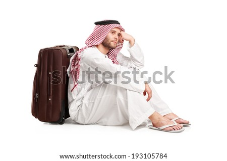 Sad Arabic man sitting on the floor with a bag behind his back isolated on white background