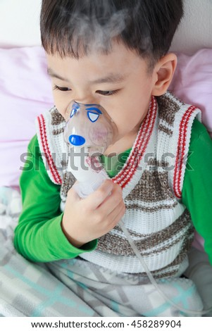 Sad asian child holds a mask vapor inhaler for treatment of asthma on sickbed in hospital. Breathing through a steam nebulizer. Concept of inhalation therapy apparatus. - stock photo