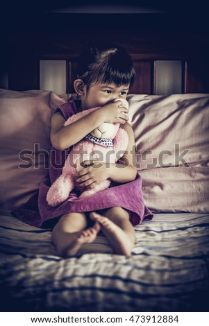 Sad asian child sitting alone on bed with doll in dark bedroom at home