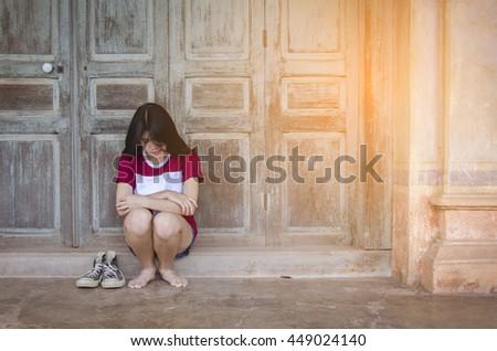 Sad asian woman sit with sunrise.  she sad she regrets she alone - stock photo