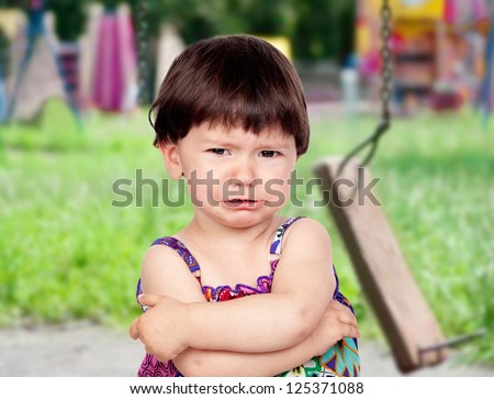 Sad baby girl crying in the park with the swing broken - stock photo