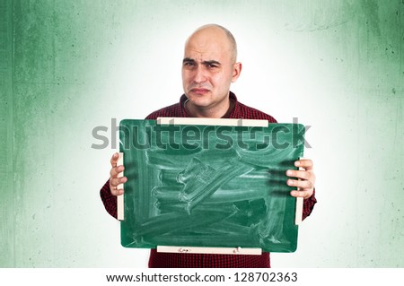 Sad bald young adult man holding a small green chalkboard.