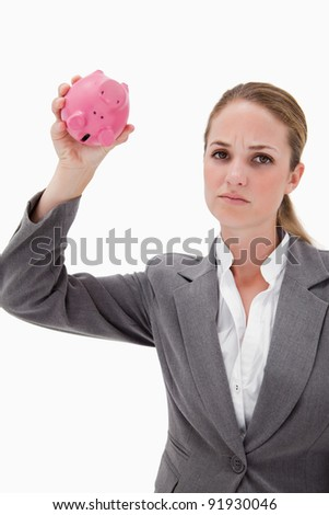 Sad bank employee with empty piggy bank against a white background - stock photo