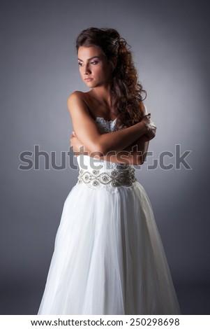 Sad beautiful bride hugging herself - stock photo