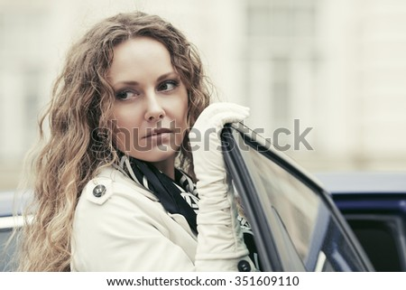 Sad beautiful fashion woman with long curly hairs by her car  - stock photo