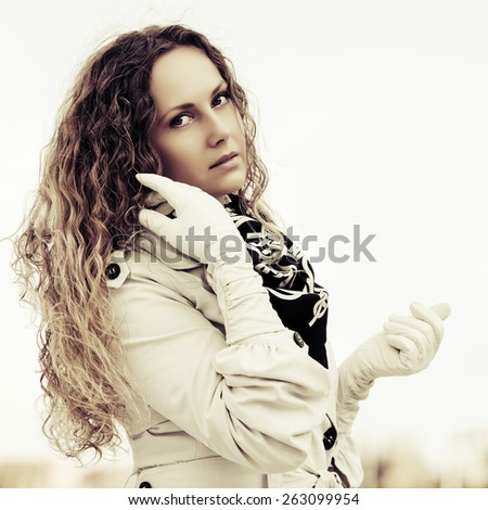 Sad beautiful fashion woman with long curly hairs outdoor - stock photo