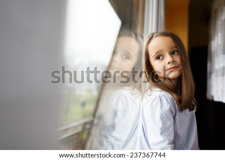 Sad Beautiful little girl watching out the window. A child looks out the window. Young girl looking from window. Portrait of sad kid sits at windowsill. - stock photo