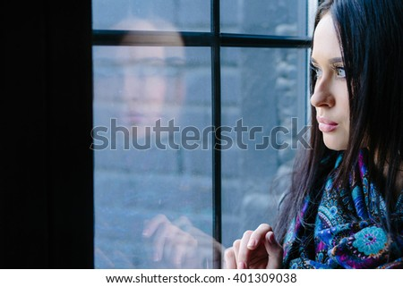 Sad beautiful woman looking out the window and thinking about something - stock photo