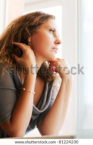 Sad beautiful woman looking through a window - stock photo