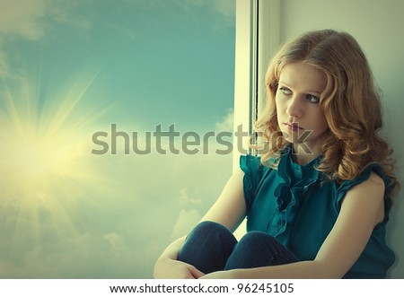 sad, beautiful young woman pining at the window at the sky and sunset - stock photo
