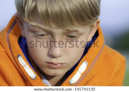 sad blonde boy in a bright orange sweatshirt