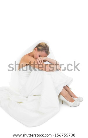 Sad blonde bride sitting on floor hiding her face - stock photo