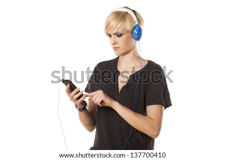 sad blonde with short hair and with questionable gestures can not find her favorite song on her phone - stock photo