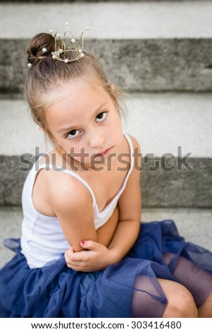 sad / bored / angry little princess with golden crown on her head. Selective focus. - stock photo