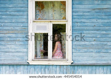 Sad bored little girl sitting on the sill and looking out the country house window. Outside view - stock photo