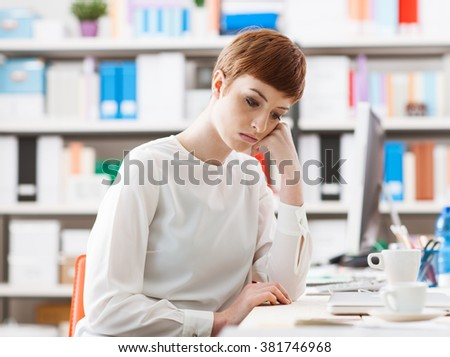 Sad bored woman sitting at office desk, she is depressed, looking down and leaning on her hand
