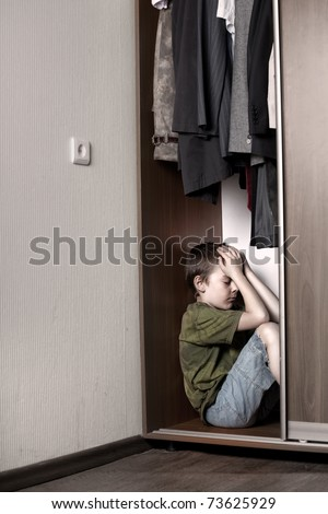 Sad boy, hiding in the closet at home - stock photo