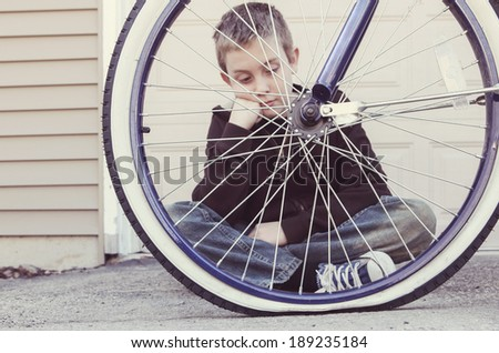 Sad boy looking at his flat bike tire - stock photo