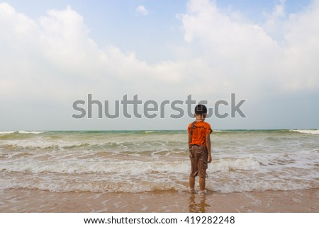 Sad boy on the beach. - stock photo