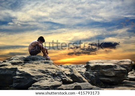 Sad boy on the rock and sky sunset.Concept drought