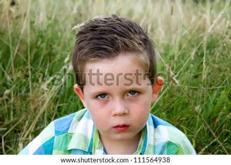 sad boy scowling whilst looking ahead - stock photo