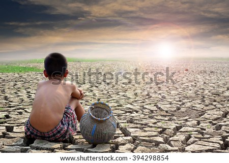 Sad boy sitting on dry ground and sunset . hope,drought - stock photo