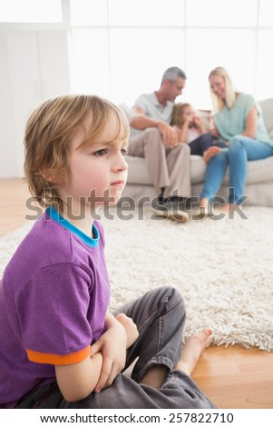 Sad boy sitting on floor while parents enjoying with sister on sofa at home - stock photo