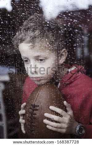Sad boy wanting to play outside - stock photo