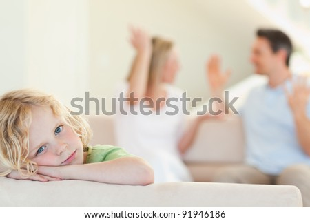 Sad boy with his fighting parents in the background - stock photo