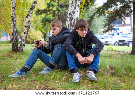 Sad Boys sit under Tree in the Autumn Park